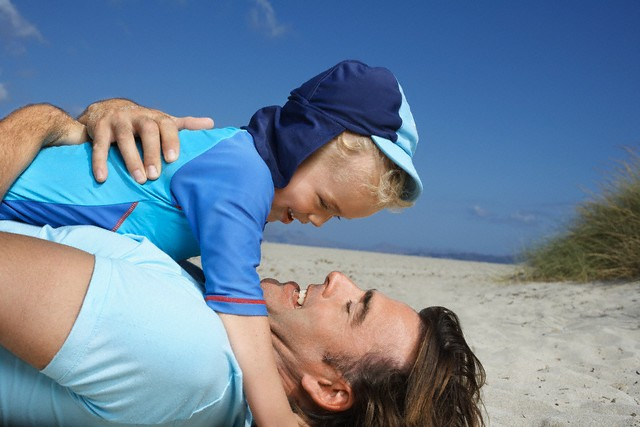 Father with Son on Chest at Beach